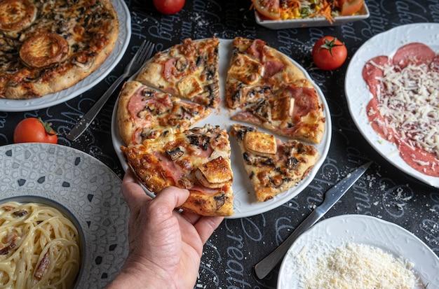 A mão do convidado pega uma fatia de pizza na mesa do restaurante