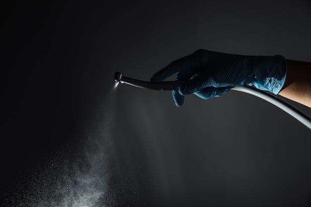 A mão do dentista com broca ilustra a operação da máquina de broca dental do dentista com água