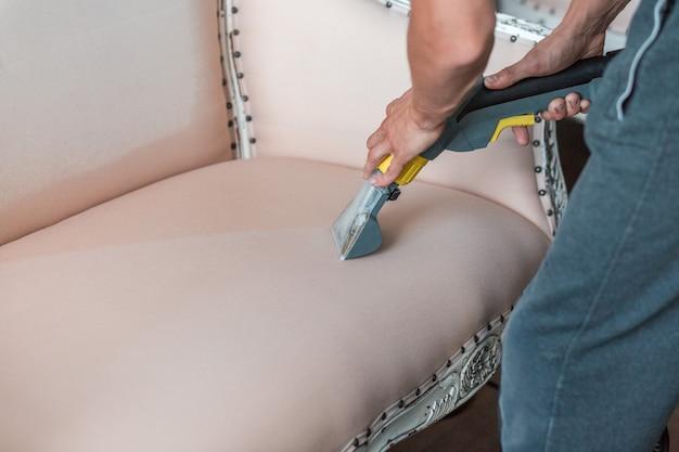 A mão do empregado de limpeza a seco está limpando o sofá clássico com método profissionalmente da extração.