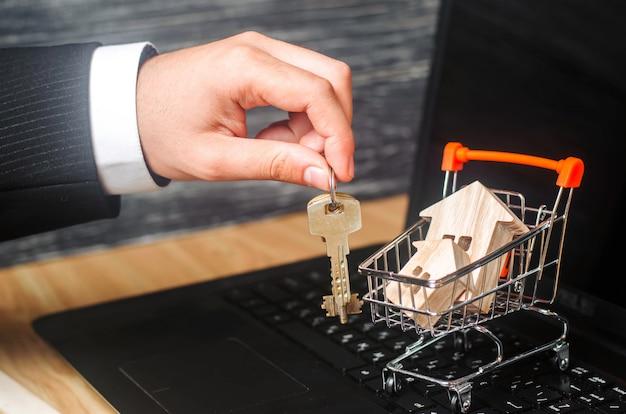 A mão do empresário detém as chaves perto do carrinho de mão com as casas.
