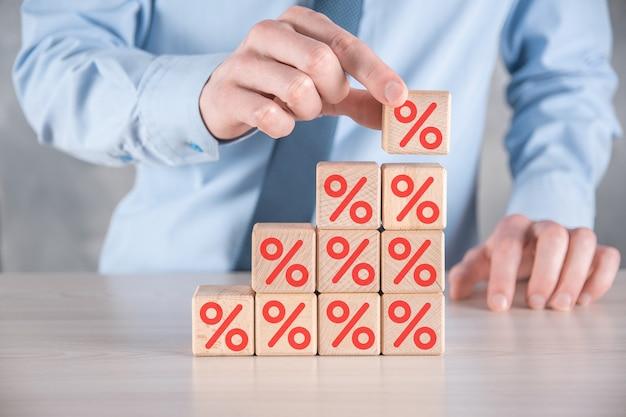 A mão do empresário pega um bloco de cubo de madeira representando, mostrado o ícone do símbolo de porcentagem. conceito de taxas financeiras e hipotecas de taxa de juros.