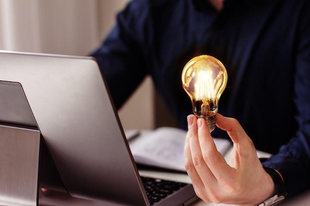 A mão do empresário segura uma lâmpada acesa, ideia, inovação e inspiração de conceito