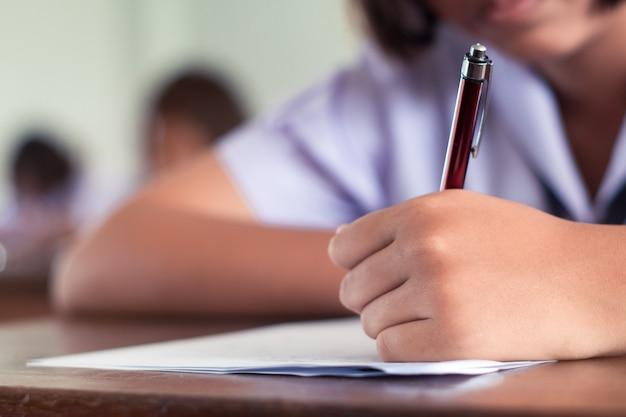 A mão do estudante está tomando o exame e está escrevendo a resposta na sala de aula