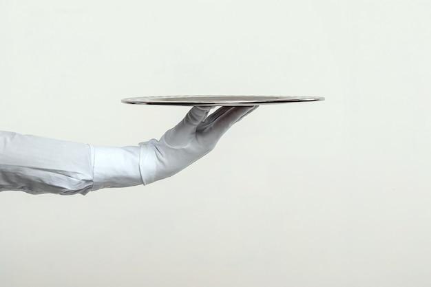A mão do garçom com luvas brancas segura uma bandeja de prata.