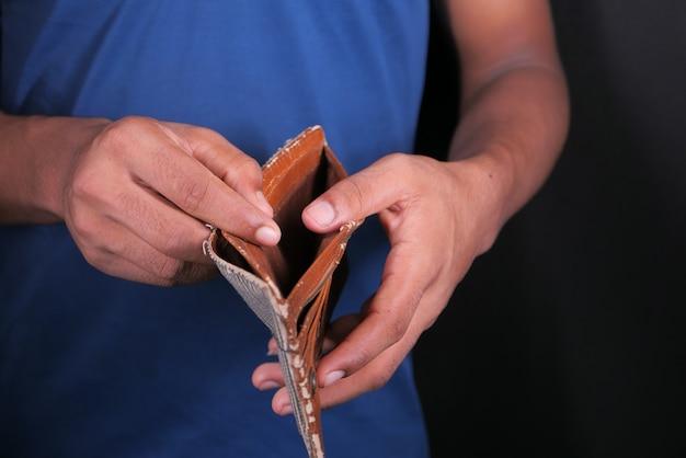 A mão do homem abre uma carteira vazia com espaço de cópia.