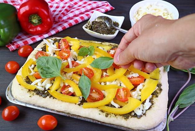 A mão do homem adiciona coberturas frescas e saudáveis na massa da pizza antes de assar