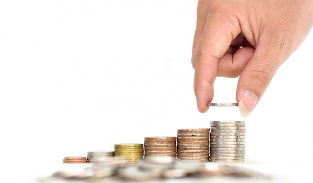 A mão do homem coloca moedas de dinheiro na pilha de moedas