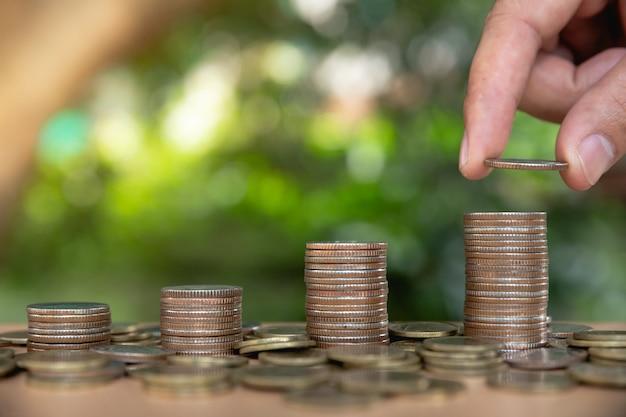 A mão do homem coloca moedas de dinheiro para a pilha de moedas