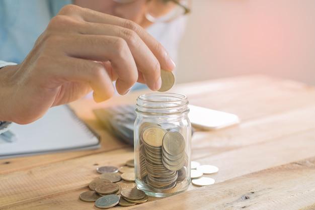 A mão do homem colocando moedas de poupança em vidro na mesa de trabalho de madeira com uma pilha de moedas, caderno, smartphone e gráfico - investimento, negócios, finanças e bancos