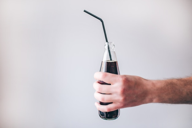 A mão do homem com a garrafa isolada. saboroso coque açucarado delicioso com palha de plástico. beba água gaseificada.