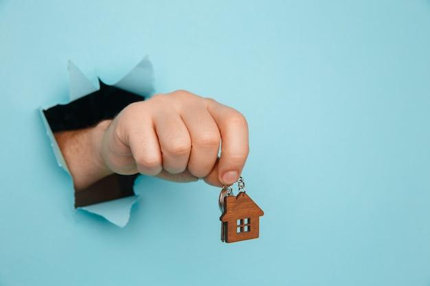 A mão do homem com as chaves da casa através de um buraco em um close-up de papel azul. conceito de venda e aluguel de casa.