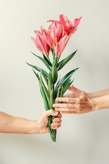 A mão do homem dando buquê de flores de lírios para a mão do woma