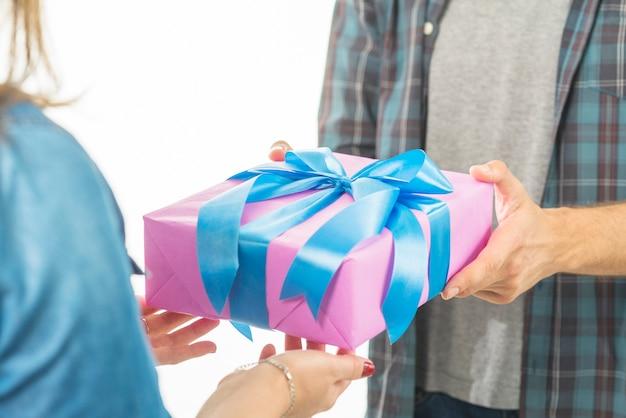 A mão do homem dando presente de dia dos namorados para sua namorada