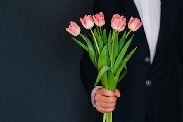 A mão do homem dando um buquê de tulipas cor de rosa