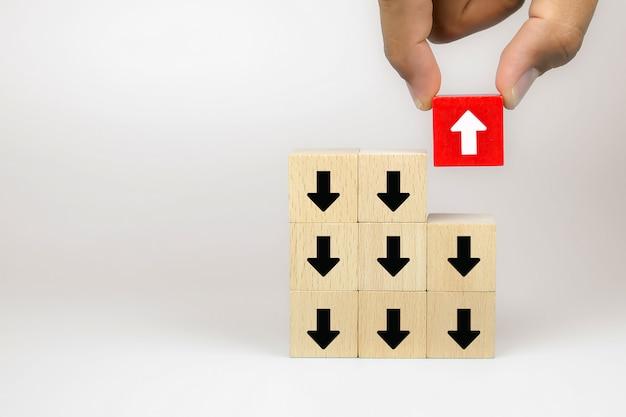 A mão do homem de negócios escolhe o cubo de madeira blog brinquedo com ícones da seta, conceito do negócio para a mudança.
