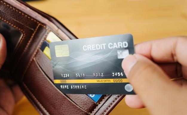 A mão do homem de negócios está pegando o cartão de crédito da carteira