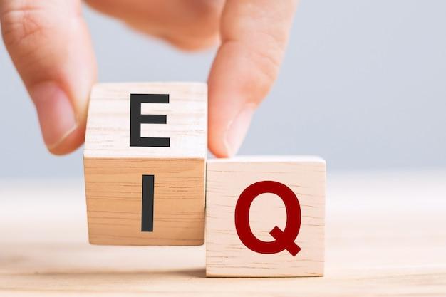 A mão do homem de negócios muda o bloco de cubos de madeira de qi para qe, equilíbrio entre quociente de inteligência e conceitos de inteligência emocional