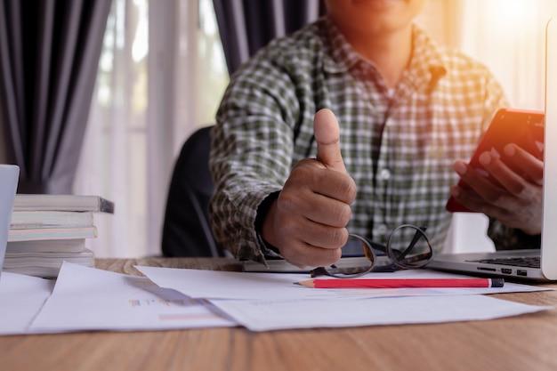 A mão do homem de negócios que mostra o polegar acima - como o sinal.