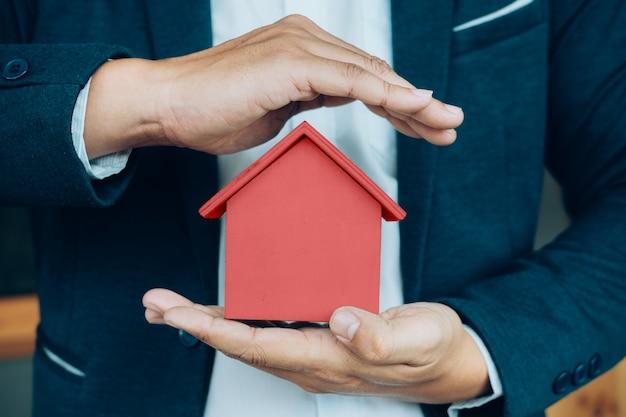 A mão do homem de negócios segura o modelo da casa que poupa uma pequena casa.