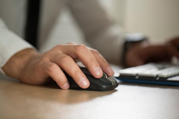 A mão do homem de negócios usa o rato do computador e a datilografia, formulário do acordo da parceria grampeado para almofada o close up. sucesso nos negócios, contrato e documento importante, papelada ou conceito de advogado