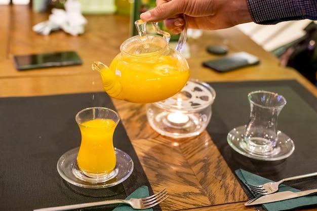 A mão do homem derrama chá de mel de espinheiro-mar do bule de vidro em uma xícara de vidro close-up foco suave