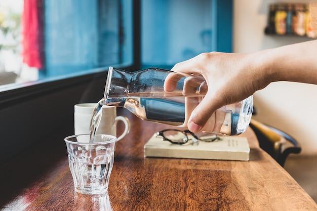 A mão do homem derramando água fresca do jarro em um copo no café.