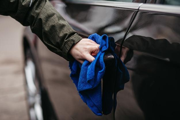 A mão do homem desinfetando a maçaneta da porta do carro marrom com um pano azul desinfetante.