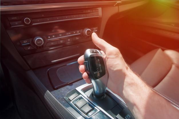 A mão do homem em uma caixa de velocidades automática.