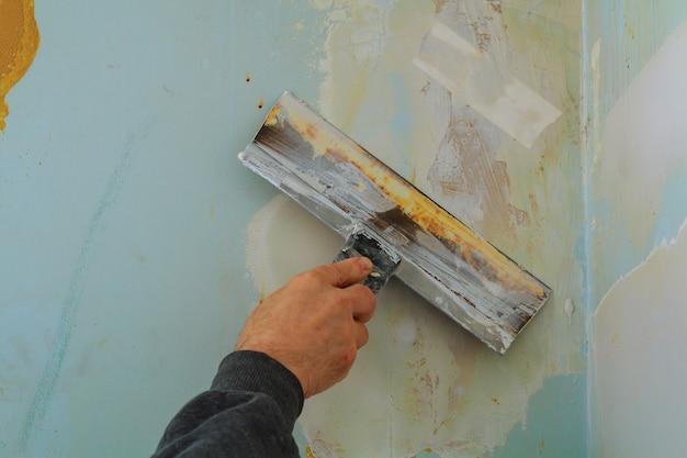 A mão do homem em uma luva cinza com espátula na sala de reparação.