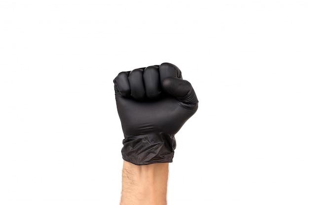 A mão do homem em uma luva preta está cerrada em um punho.