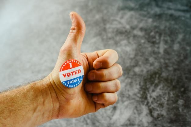A mão do homem ensinando que ele votou hoje nas eleições americanas com um adesivo.