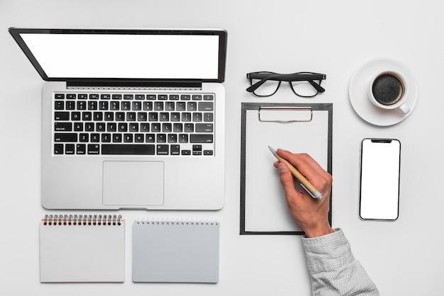 A mão do homem, escrevendo na área de transferência perto de laptop no escritório