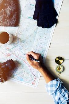 A mão do homem escrevendo no mapa com acessórios de viagem na mesa de madeira