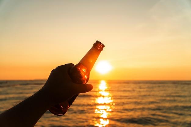 A mão do homem está guardando a garrafa de cerveja e mantém sua mão no céu na noite com por do sol.