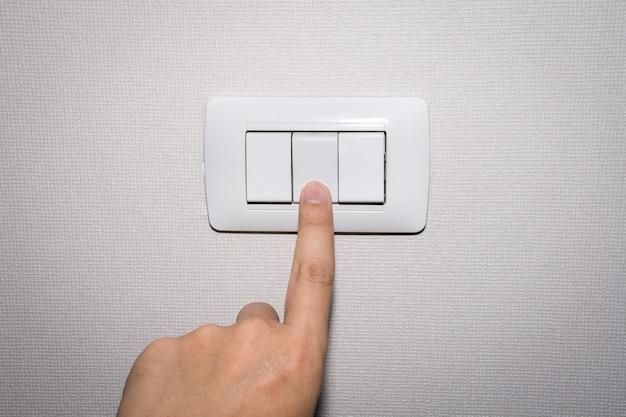 A mão do homem está ligando ou desligando o interruptor de luz elétrica.