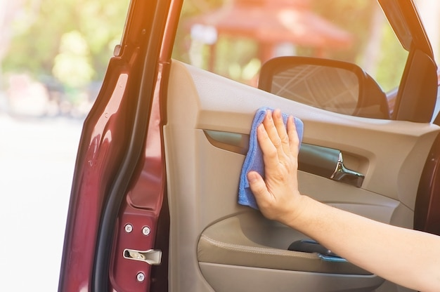 A mão do homem está limpando e encerando o carro