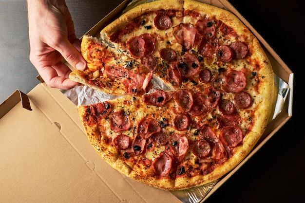 A mão do homem está segurando a fatia de pizza de queijo de todo pizza no fundo de mesa escura de caixa de papelão