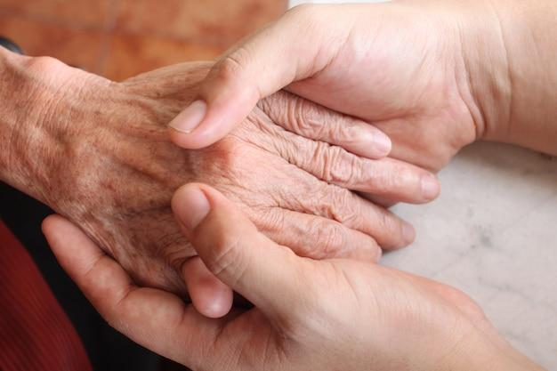 A mão do homem está segurando a mão da velha.