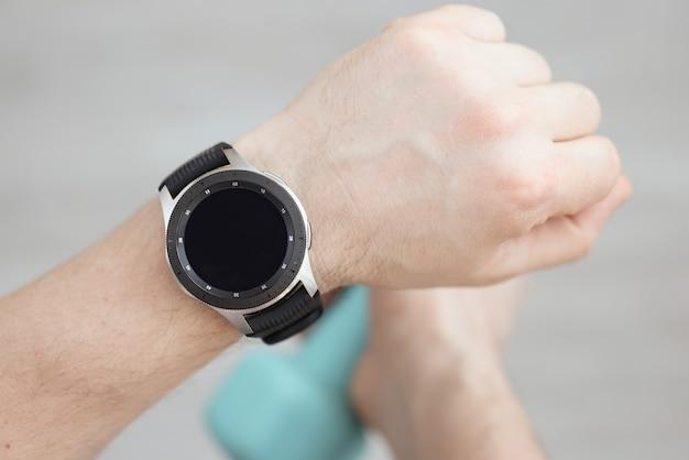 A mão do homem está usando um relógio inteligente, na outra, ele está segurando um haltere