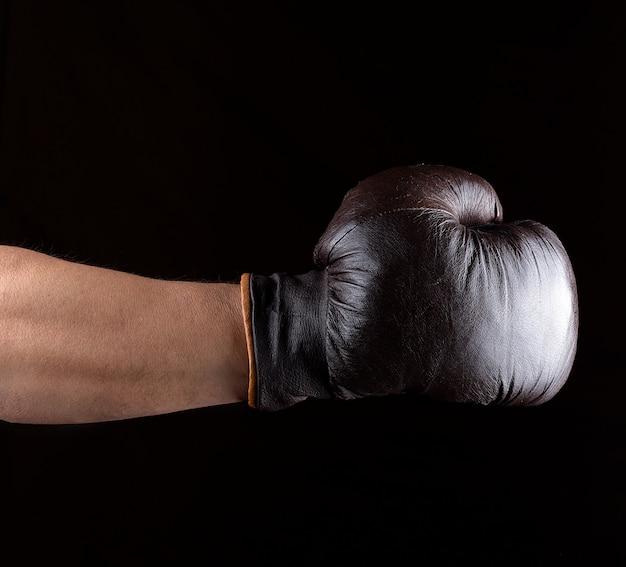 A mão do homem está usando uma luva de boxe de couro marrom