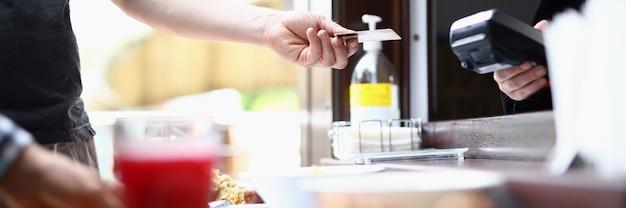 A mão do homem estende o cartão do banco sem contato ao caixa para pagar o almoço