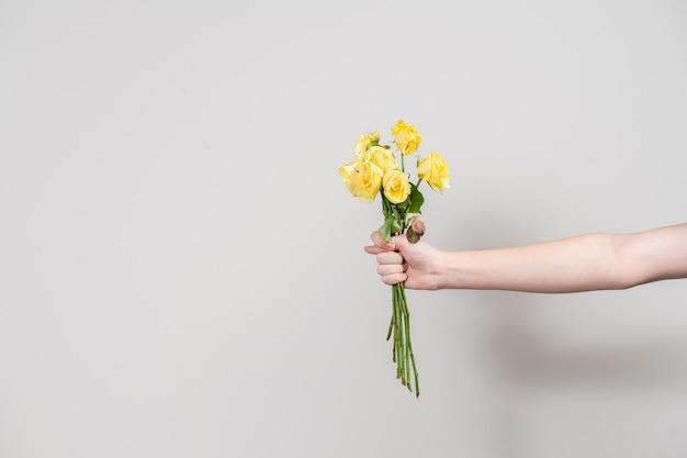 A mão do homem estende um buquê de flores murchas e mostra um figo. conceito de separação. layout com lugar para texto