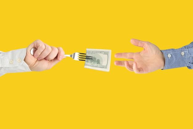 A mão do homem estende um garfo com uma nota de um dólar na outra mão no amarelo