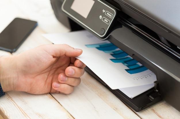 A mão do homem fazendo cópias. trabalhando com impressora