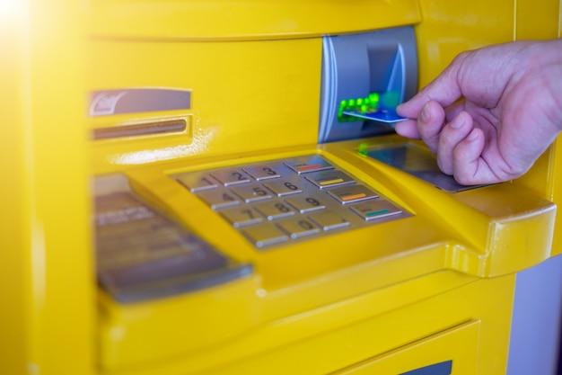 A mão do homem inserir um cartão de crédito no caixa eletrônico