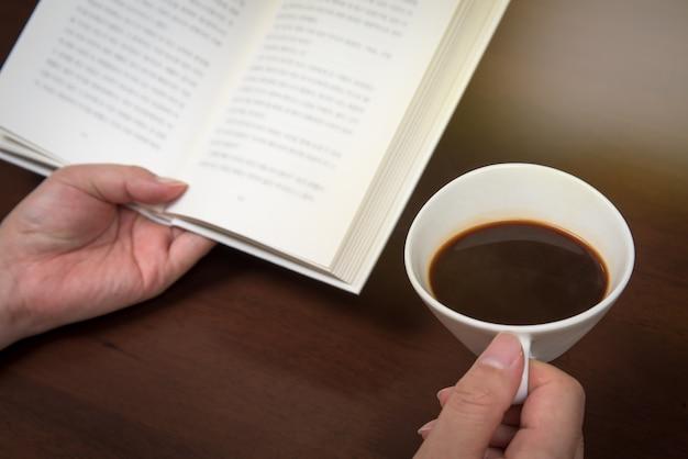 A mão do homem lendo com uma xícara de café em uma mão.