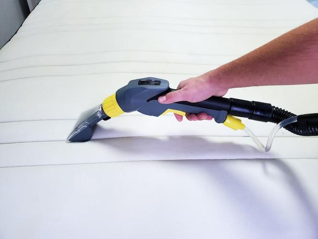 A mão do homem limpa um colchão branco moderno com um agente de limpeza profissional
