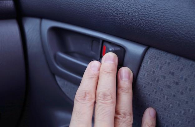 A mão do homem na alça interna do carro moderno