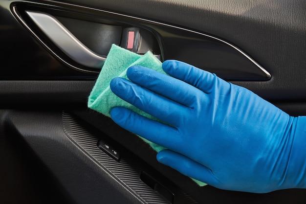 A mão do homem na luva protetora azul está limpando com um pano um puxador interior da porta do carro. proteção contra coronavírus ou covid-19.