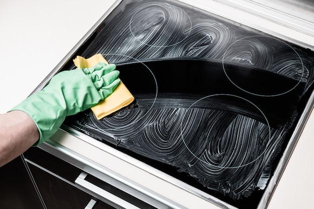 A mão do homem na luva verde limpeza fogão em casa cozinha